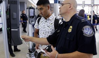 In a June 29, 2017, photo, U.S. Customs and Border Protection Officer Sanan Jackson, right, helps a passenger navigate the new face recognition kiosks at gate E7 for a United Airlines flight to Tokyo at Bush Intercontinental Airport in Houston. The Trump administration intends to require that American citizens boarding international flights submit to face scans, something Congress has not explicitly approved and privacy advocates consider an ill-advised step toward a surveillance state. (Michael Wyke/Houston Chronicle via AP)