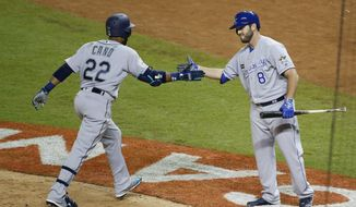 American League's Seattle Mariners Robinson Cano (22), is congratulated by Kansas City Mike Moustakas, after Cano hit a home run in the tenth inning, during the MLB baseball All-Star Game, Tuesday, July 11, 2017, in Miami. (AP Photo/Wilfredo Lee)