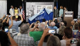 A display of Andrew Wyeth Forever stamps is unveiled during a First-Day-of-Issue dedication ceremony at the Brandywine River Museum of Art, Wednesday, July 12, 2017, in Chadds Ford, Pa. The panel of 12 Forever stamps feature details from different iconic Andrew Wyeth paintings. (AP Photo/Matt Slocum)