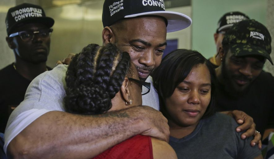 Jabbar Washington, 43, center, hugs his mother Martha Washington, left, and daughter Jasmine, 21, before a news conference at Brooklyn Supreme Court, Wednesday July 12, 2017, in New York. Washington, who spent 21 years behind bars for murder, was set free after prosecutors abandoned his conviction, acknowledging jurors got misleading testimony from an eyewitness. (AP Photo/Bebeto Matthews)