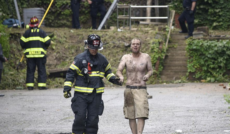 A man is helped by emergency personnel after he was rescued from a partially collapsed building, Wednesday July 12, 2017, in Washington, Pa. (Celeste Van Kirk/Observer-Reporter via AP)