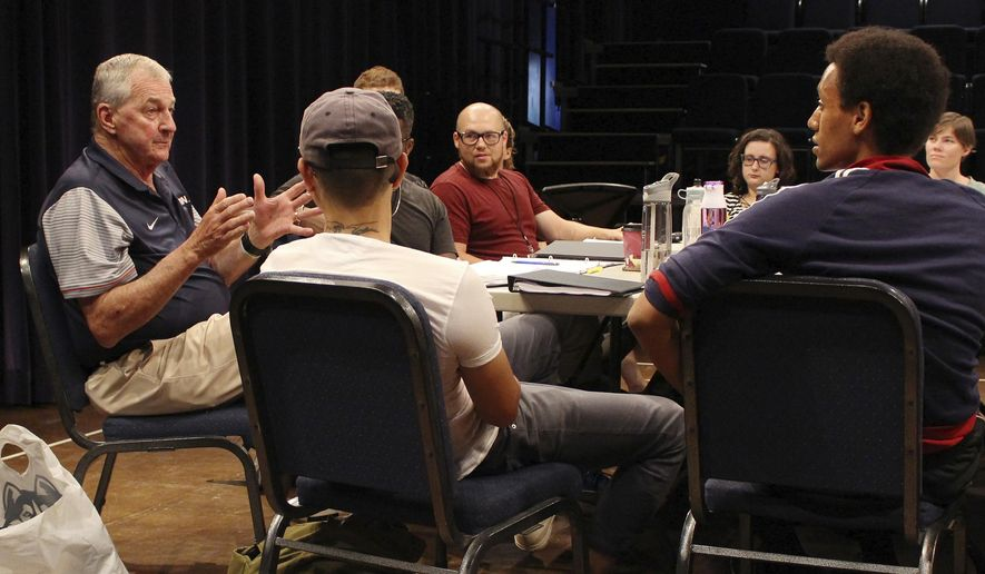 "Former UConn NCAA college basketball coach Jim Calhoun, left, gestures as he answers a question from actor Sam Kebebe, right, during a meeting with the cast and crew of the play ""Exposure"" at the Eugene O'Neill Theater Center, Tuesday, July 11, 2017, in Waterford, Conn. Calhoun is serving as an adviser for the play about the darker side of college basketball recruiting. (AP Photo/Pat Eaton-Robb)"