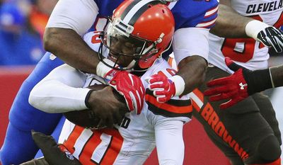 In this Dec. 18, 2016, photo, Buffalo Bills defensive end Adolphus Washington (92) sacks Cleveland Browns quarterback Robert Griffin III (10) during the second half of an NFL football game in Orchard Park, N.Y. Washington has been arrested in Ohio on a weapons charge. He was processed at the Sharonville Police Department and released. The Bills released a statement Monday night, July 10, 2017, saying they're aware of the situation and have been in contact with Washington. (AP Photo/Bill Wippert)