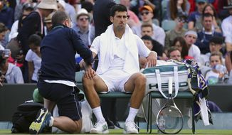 Novak Djokovic receives medical treatment during his Men's Singles Match against Tomas Berdych on day nine of the Wimbledon Tennis Championships at The All England Lawn Tennis and Croquet Club, London, Wednesday, July 12, 2017. (Gareth Fuller/PA via AP)