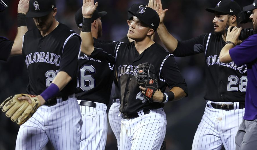 FILE - In this July 5, 2017, file photo, Colorado Rockies shortstop Pat Valaika, center, and teammates celebrate a 5-3 win over the Cincinnati Reds in a baseball game, in Denver. Despite a recent slump, the Colorado Rockies are in prime position to make the postseason for the first time since 2009. (AP Photo/David Zalubowski, File)