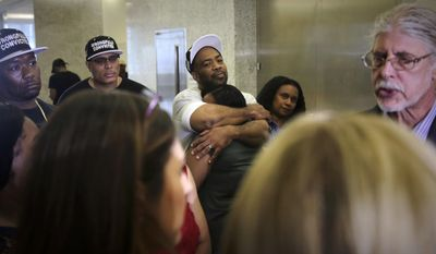 Jabbar Washington, 43, center, hugs his daughter Jasmine, 21, while listening to his lawyer Ron Kuby, far right, during a press conference at Brooklyn Supreme Court, Wednesday July 12, 2017, in New York. Washington, who spent 21 years behind bars for murder, was set free after prosecutors abandoned his conviction, acknowledging jurors got misleading testimony from an eyewitness. (AP Photo/Bebeto Matthews)