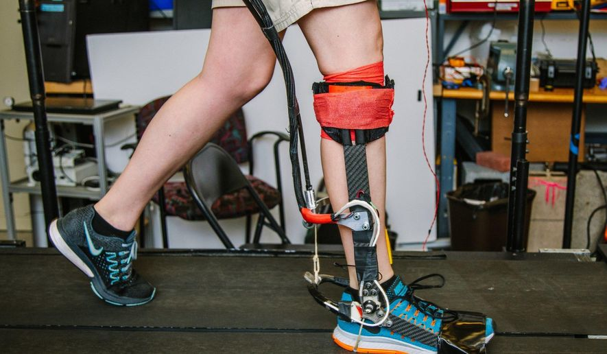 In a June 22, 2017 photo, Kirby Witte, a Ph.D. student in mechanical engineering, tests a prototype of an exoskeleton in a lab at Carnegie Mellon University. Her team is working on exoskeleton research that will improve walking, including the ability to adapt to the walking technique of each individual. (Andrew Rush/Pittsburgh Post-Gazette via AP)