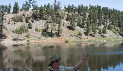 In this June 6, 2017 photo, archeologist Doug Kosick leads a discussion on environmental history with a group of environmentalists during a field tour at McGaffey Lake about 20  miles southeast of Gallup, N.M. (Morgan Hornsby/Gallup Independent via AP)