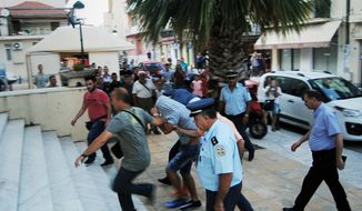 In this Saturday, July 8, 2017 photo , policeman lead suspects as they enter the court, in Zakynthos island, Greece. Eight suspects charged with involvement in the beating to death of a 22-year-old American tourist on a Greek island were granted brief delays in court appearances Tuesday to allow their lawyers to prepare their cases, while authorities have arrested a ninth man. The hearings for six Serbs, a British citizen of Serb origin and a Greek were postponed for Wednesday and Thursday. (imerazande.gr via AP)
