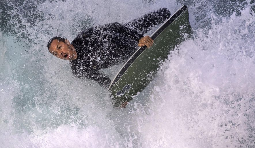 A surfer rides the waves at The Wedge in Newport Beach, Calif., Tuesday, July 11, 2017. Large surf is expected along much of the Southern California coast and beachgoers are warned of dangerous waves and rip currents.(Mindy Schauer/The Orange County Register via AP)