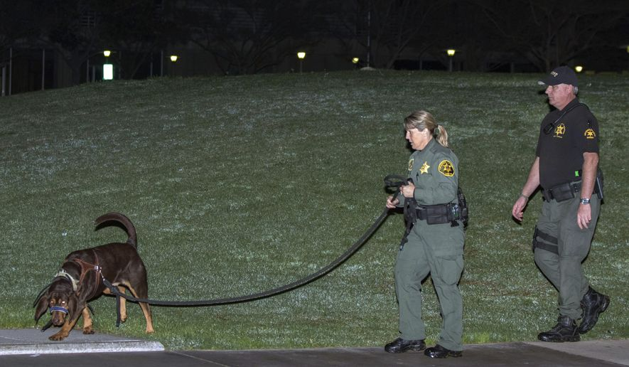 FILE - In this Jan. 23, 2016 file photo, Orange County sheriff's deputies and a search dog investigate early after three jail inmates charged with violent crimes escaped from Central Men's Jail in Santa Ana, Calif. Orange County Sheriff's officials Tuesday, July 12, 2017, conceded that inadequate staffing and management of the jail played a key role in the brazen escape of a trio of inmates last year. A sheriff's department document shows since then officials have hired nearly 22 new deputies at the jail. Sheriff Sandra Hutchens recently said she agrees with a grand jury panel report that found jail staff ignored security rules and took shortcuts in counting inmates. (AP Photo/Kevin Warn, File)