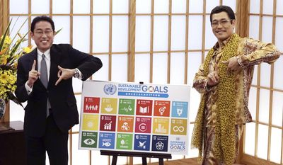 "Japanese comedian Pikotaro, right, and Japan's Foreign Minister Fumio Kishida pose to raise awareness about the United Nation's 17 Sustainable Development Goals (SDGs) at the ministry in Tokyo, Wednesday, July 12, 2017. Pikotaro, who has gained global fame with his ""pen-pineapple-apple-pen"" song, will debut at the United Nations with a new version of PPAP to promote sustainable development.(AP Photo/Eugene Hoshiko)"