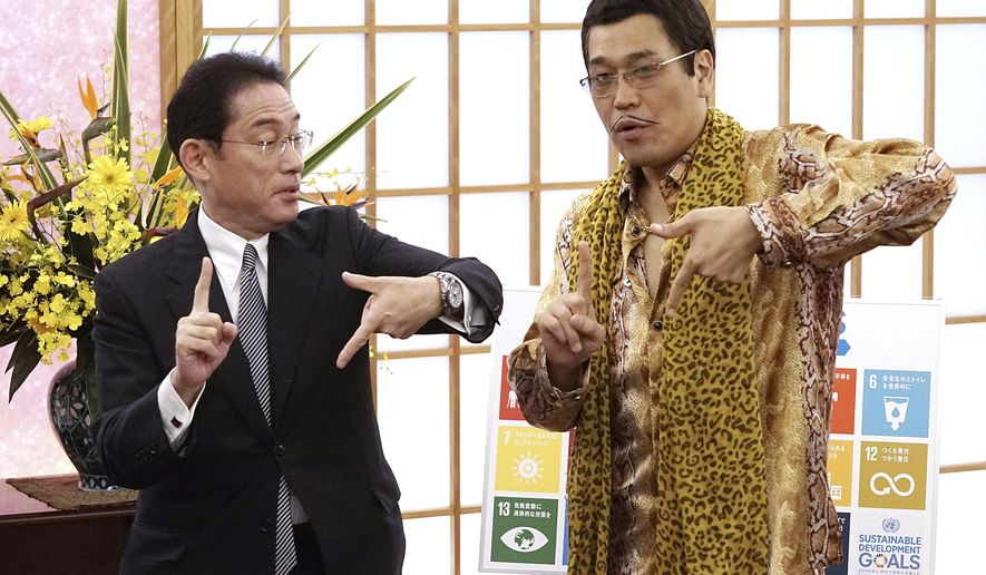 "Japanese comedian Pikotaro, right, and Foreign Minister Fumio Kishida pose to raise awareness about the United Nation's 17 Sustainable Development Goals (SDGs) at the ministry in Tokyo, Wednesday, July 12, 2017. Pikotaro, who has gained global fame with his ""pen-pineapple-apple-pen"" song, will debut at the United Nations with a new version of PPAP to promote sustainable development.(AP Photo/Eugene Hoshiko)"