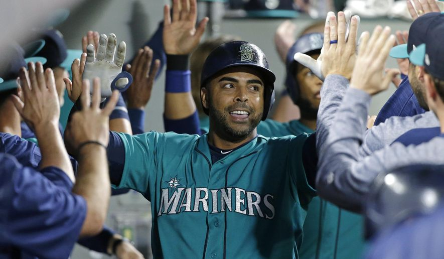 FILE - In this July 7, 2017, file photo, Seattle Mariners' Nelson Cruz is greeted in the dugout after he hit a three-run home run during the eighth inning of the team's baseball game against the Oakland Athletics, in Seattle. Cruz is leading the American League in RBIs with 70 at the break despite playing through leg injuries during big chunks of the first half. (AP Photo/Ted S. Warren, File)