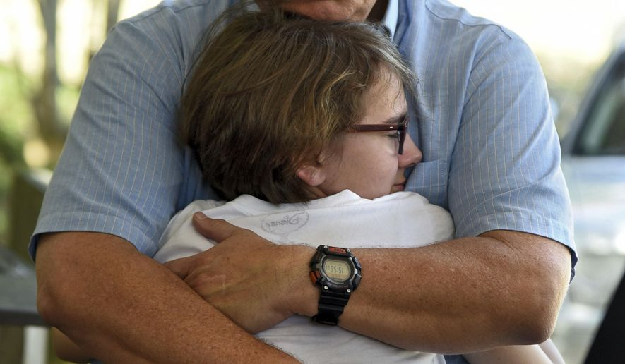 Terry Murray hugs his daughter Grace, 18, after speaking on behalf of his family about the loss of his son, Marines Sgt. Joseph Murray, at a press conference in Jacksonville, Fla., Wednesday, July 12, 2017. Sgt. Murray was one of the Marines killed in a plane crash Monday in Mississippi. (Bob Mack/The Florida Times-Union via AP)