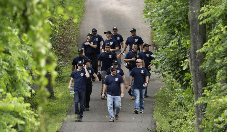 Law enforcement workers walk down a blocked off drive way in Solebury, Pa., as the search resumes Tuesday, July 11, 2017, for four missing young Pennsylvania men feared to be the victims of foul play.  (AP Photo/Matt Slocum)