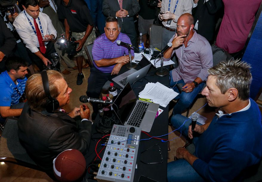 Alabama NCAA college football coach Nick Saban speaks with former Auburn and NFL player Al Del Greco (center left) and former Alabama and NFL player Jay Barker (center right) on a radio show during the Southeastern Conference's annual media gathering, Wednesday, July 12, 2017, in Hoover, Ala. (AP Photo/Butch Dill)