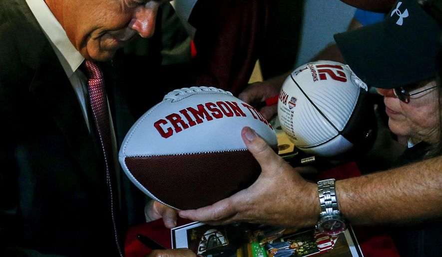 Alabama NCAA college football coach Nick Saban signs an autograph for fans during the Southeastern Conference's annual media gathering, Wednesday, July 12, 2017, in Hoover, Ala. (AP Photo/Butch Dill)