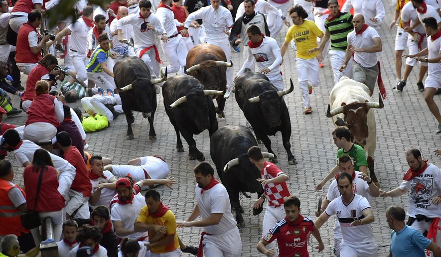 Revellers run in front of Jandilla's fighting bulls during the running of the bulls at the San Fermin Festival, in Pamplona, northern Spain, Wednesday, July 12, 2017. Revellers from around the world flock to Pamplona every year to take part in the eight days of the running of the bulls. (AP Photo/Alvaro Barrientos)