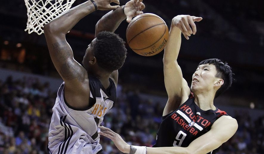 FILE - In this Monday, July 10, 2017, file photo, Houston Rockets' Zhou Qi, right, of China, fouls Phoenix Suns' Marquese Chriss during the second half of an NBA summer league basketball game in Las Vegas. When the Rockets signed Zhou and the Dallas Mavericks brought in Ding Yanyuhang to play on their summer league teams, there was some cynicism the moves were purely financially motivated for teams to tap more directly into the lucrative Chinese market. But little by little both are playing like they belong at the NBA's summer league. (AP Photo/John Locher, File)