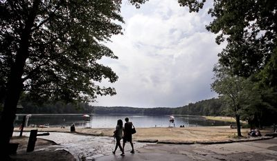 "A couple walks along the shore of Walden Pond in Concord, Mass., Wednesday, July 12, 2017. Author Henry David Thoreau, who was born in Concord 200 years ago on July 12, 1817, wrote of the beauty of the pond, woods and landscape of the area while living simply in his book ""Walden."" (AP Photo/Charles Krupa)"