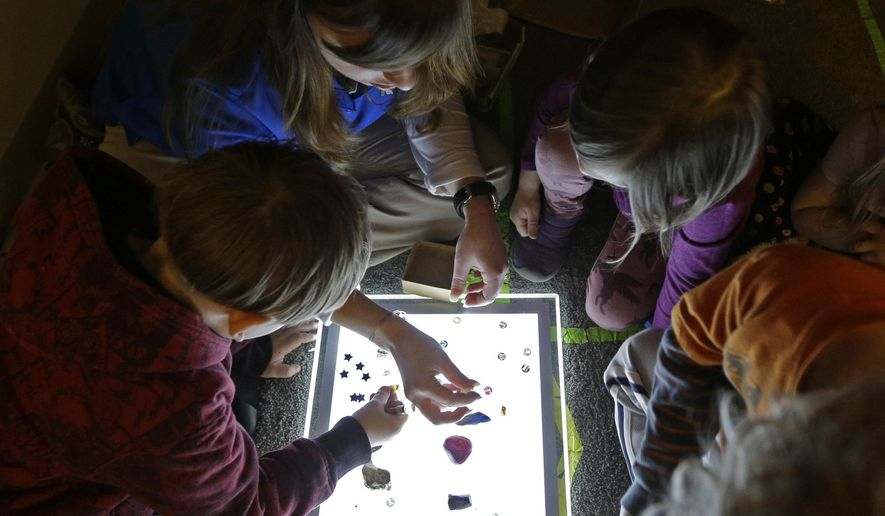 Amy Band, top, shows children items on a lightbox at the Verner Center in Asheville, N.C., on March 23, 2017. Safe spaces, quiet times and breathing exercises for the preschoolers are designed to help kids cope with intense stress so they can learn. (AP Photo/Chuck Burton)