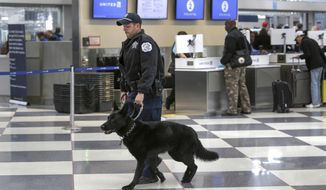 FILE - In this March 22, 2016, file photo, a Chicago Police K-9 officer and his dog walk through a terminal at O'Hare International Airport in Chicago. The Chicago Department of Aviation announced Wednesday, July 12, 2017, a new directive designating Chicago Police officers as the lead on all disturbance calls at the airports, in addition to those on aircrafts. This new directive comes after the CDA's review of the Aviation Security Division after a United passenger was forcibly removed by Aviation Security officers in April. (AP Photo/Teresa Crawford, File)