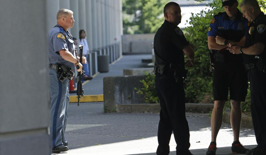 A Washington State Patrol trooper holds a gun after a lockdown at the state Capitol campus in Olympia, Wash. was lifted, Wednesday, July 12, 2017. The Patrol said in an email alert that troopers conducted a thorough search of buildings on campus Wednesday after reports of suspicious noises, but that nothing was found. (AP Photo/Ted S. Warren)