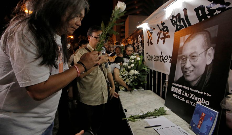 Protesters mourn jailed Chinese Nobel Peace laureate Liu Xiaobo during a demonstration outside the Chinese liaison office in Hong Kong, on Thursday. He was died of liver cancer a few weeks after his release from prison. (Associated Press)