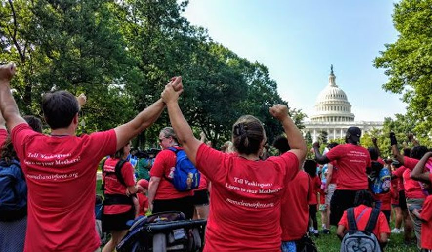 """Supporters of """"Moms Clean Air Force"""" raise their fists in defiance of proposed EPA budget cuts by the Trump administration during a rally on the Upper Senate Park grounds on Capitol Hill on Thursday. (Photographs by Emma Ayers/The Washington Times)"""