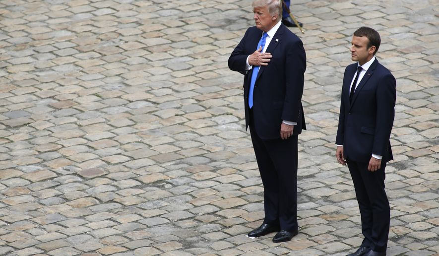 French President Emmanuel Macron and US President Donald Trump listen to the national anthems as part of an official welcoming ceremony in the courtyard of the Invalides in Paris, Thursday, July 13, 2017. Trump is in Paris for a high profile two-day visit during which he will be the guest of honour of his French counterpart Emmanuel Macron at the annual Bastille Day parade. (AP Photo / Matthieu Alexandre)