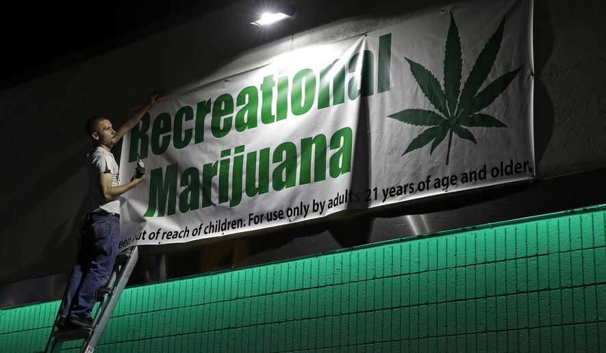 In this June 30, 2017, file photo, Bryce Tallitsch hangs up a sign for recreational marijuana at the NuLeaf dispensary in Las Vegas. (AP Photo/John Locher, File)