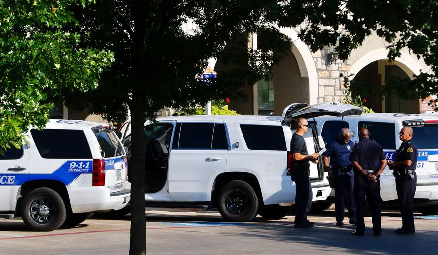 Dallas police respond respond to a standoff Thursday, July 13, 2017 in Dallas. Police surrounded an apartment complex after someone in a residence fired a shot through a front door at officers trying to serve an aggravated assault warrant. (David Woo/The Dallas Morning News via AP)
