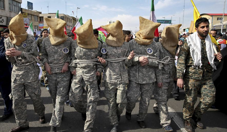 FILE - In this Feb. 11, 2016 file photo, members of the Iranian Basij paramilitary force reenact the January 2016 capture of U.S sailors by the Revolutionary Guard in the Persian Gulf, in a rally commemorating the 37th anniversary of Islamic Revolution, in Tehran, Iran. Mohsen Dehnavi, an Iranian cancer researcher who was denied entry to the U.S. previously headed a student branch of a volunteer paramilitary militia, footage aired on state television Thursday, July 13, 2017, showed. In comments to the channel at the Tehran airport, he defended his travel to the United States as solely intended for science and research. (AP Photo/Ebrahim Noroozi, File)
