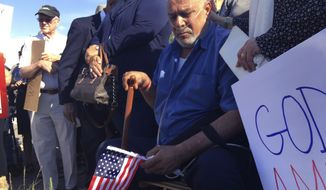 FILE - In this June 26, 2017 file photo Kadhim Al-bumohammed, center, an Iraqi refugee in the U.S., listens to speakers at an Albuquerque, N.M., rally in his honor. Al-bumohammed an Iraqi Muslim refugee who trained U.S. troops going to Iraq and is now facing deportation is seeking sanctuary inside an Albuquerque church. Al-bumohammed decided to skip his immigration hearing Thursday, July 13, where he was expected to be detained. (AP Photo/Russell Contreras, File)