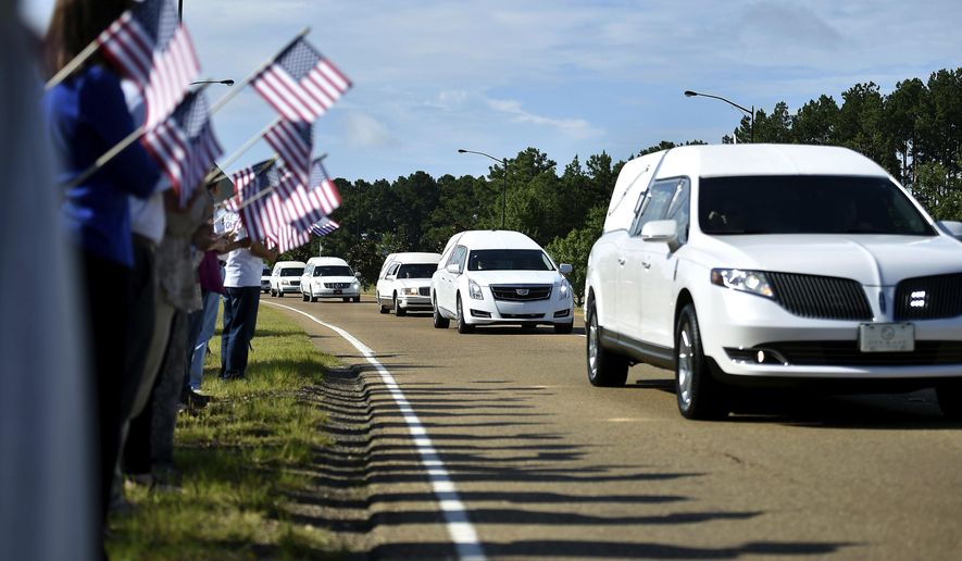 Supporters hold American flags on the side of Airport Road in Jackson, Mississippi, Thursday, July 13, 2017, as hearses carry the remains of the 16 service members who died in a plane crash in Leflore County, Mississippi Monday to the Air National Guard base for their final flights home. (Justin Sellers/The Clarion-Ledger via AP)