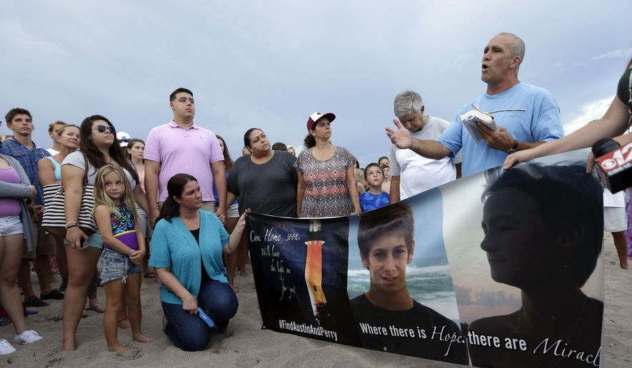 FILE - In a Tuesday, July 28, 2015 file photo, Carl Hodges, of Stuart, Fla., right, reads a prayer during a vigil for Austin Stephanos and Perry Cohen, in Stuart, Fla. , two teenagers who have been missing since they went out on a boat to go fishing from Tequesta, Fla. and never returned. U.S. District Judge William P. Dimitrouleas on Monday, July 10, 2017, lifted an injunction that kept Pamela and Philip Cohen from suing Carly Black in state court. She owned the 19-foot (6-meter) boat her son Austin Stephanos was in when he left Jupiter Inlet on July 24, 2015, with the Cohens' son Perry. (AP Photo/Lynne Sladky, File)