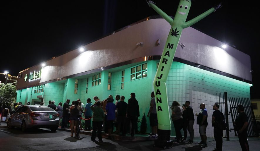 FILE- In this Saturday, July 1, 2017, file photo, people line up at the NuLeaf marijuana dispensary in Las Vegas. The Nevada Tax Commission is expected to approve an emergency regulation on Thursday, July 13, to issue distribution licenses needed to address an anticipated supply shortage in the coming weeks. (AP Photo/John Locher, File)