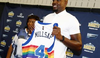 Denver Nuggets new forward Paul Millsap holds up his new jersey during his introduction to the media at a news conference Thursday, July 13, 2017, in Denver. (AP Photo/David Zalubowski)