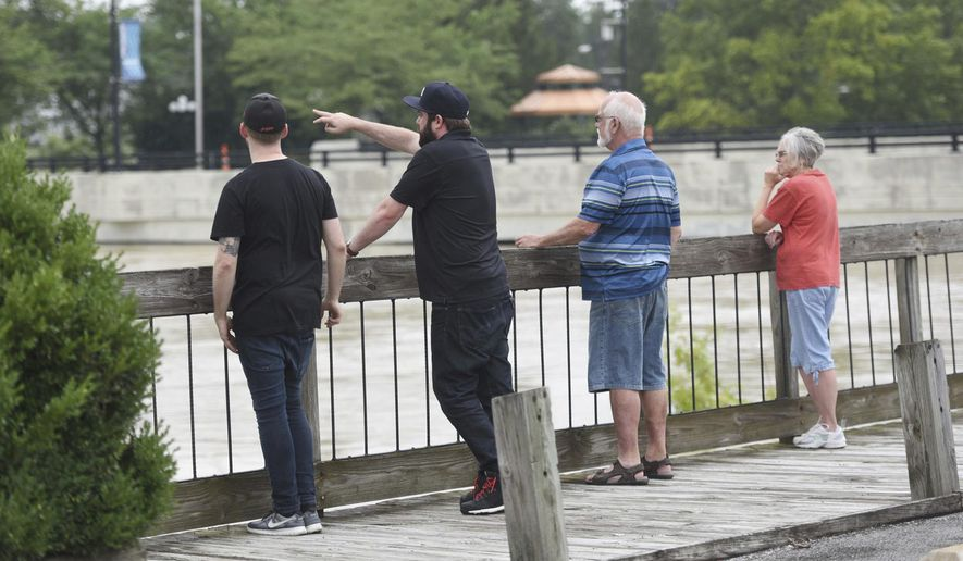Findlay residents watch as the Blanchard River rises in downtown Findlay, Ohio, Thursday, July 13, 2017.  The National Weather Service expects near-record flooding in the city by Friday morning. Many city streets already are closed because of high water. (Randy Roberts/The Courier via AP)