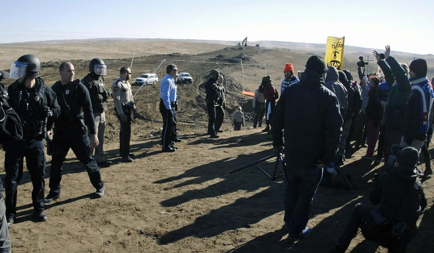"FILE - In this Nov. 11, 2016, file photo, law enforcement try to move Dakota Access pipeline protesters further down during a protest at a pipeline construction site south of St. Anthony, N.D. The Trump administration has denied a request from Republican North Dakota Gov. Doug Burgum for a ""major disaster declaration"" to help cover some of the estimated $38 million cost to police protests of the pipeline. (Mike McCleary/The Bismarck Tribune via AP, File)"