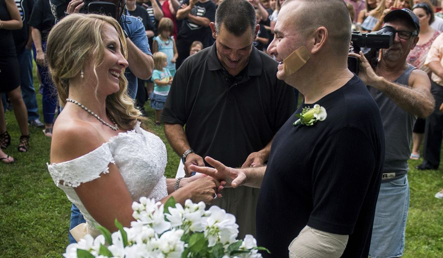 Leechburg Police Chief Mike Diebold laughs with his wife Danielle Reinke during their wedding ceremony at the Leechburg Volunteer Fire House on Wednesday, July 12, 2017 in Leechburg, Pa.  The 39-year-old chief who is also licensed to run his own fireworks business, was injured when a shell exploded June 24, losing his left hand and lower arm. Diebold was released from a Pittsburgh hospital a week before the wedding and eventually hopes to resume his police duties wearing a prosthetic limb. (Nate Smallwood/Pittsburgh Tribune-Review via AP)