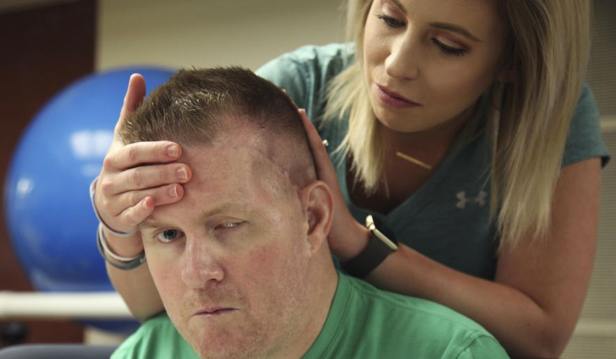 In this July 6, 2017 photo, Danielle McNicoll, fiancee of Cpl. Nick Tullier, holds his head during his physical therapy session at TIRR Memorial Hermann Hospital in Houston. Tullier was shot three times by a gunman bent on killing police officers in Baton Rouge, La., on July 17, 2016. (AP Photo/John L. Mone)