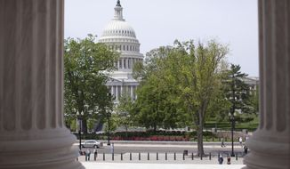 In this May 5, 2014, file photo, the Capitol building is seen through the columns on the steps of the Supreme Court in Washington. (AP Photo/Carolyn Kaster, File)
