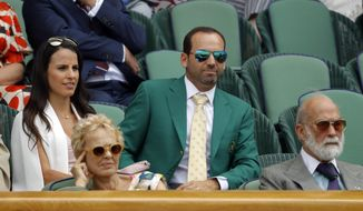 FILE - In this Friday, July 7, 2017 file photo golfer Sergio Garcia, wearing his green Masters jacket, centre and fiancee Angela Akins sit in the Royal Box on day five at the Wimbledon Tennis Championships in London. When Masters champion Sergio Garcia sat in the Royal Box at Wimbledon last week, he showed up in his green jacket from Augusta National. Seemed fitting. The tennis and golf tournaments seem to be each other's counterparts in many ways, starting with the reverence in which they're held by many in the sports. (AP Photo/Alastair Grant, File)
