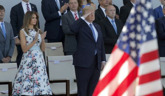 U.S. President Donald Trump salutes as he watches with his wife Melania Trump the traditional Bastille Day military parade on the Champs Elysees, in Paris, Friday, July 14, 2017. (AP Photo/Michel Euler)
