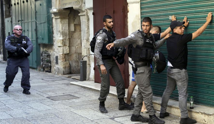 Israeli border police officers body-search Palestinians in Jerusalem's Old City, Friday, July 14, 2017. Three Palestinian assailants opened fire on Israeli police from inside a major Jerusalem holy site Friday, killing two officers before being shot dead, police said. (AP Photo/Mahmoud Illean)