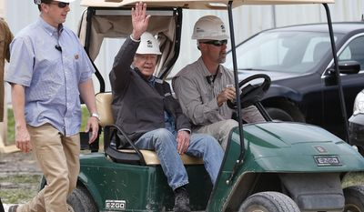 Former U.S. President Jimmy Carter waves to assembled crowd members as he returns to a Habitat for Humanity, Jimmy and Rosalynn Carter Project build site for a press conference in Winnipeg, Friday, July 14, 2017. Carter was not feeling well and had to leave the site yesterday while working with the organization. He was hospitalized for dehydration and returned to the site today. (John Woods/The Canadian Press via AP)
