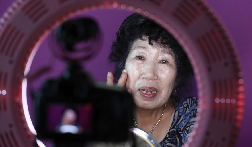 In this July 11, 2017 photo, South Korea's YouTube star, Park Makrye, 70, gives a demonstration of make-up tutorials for her YouTube channel during an interview at her home in Yongin, South Korea.  Park's videos are all about showing off her wrinkles and her elderly life in the raw. Young South Koreans find her so funny and adorable that big companies like Samsung Electronics and Lotte are banking on her popularity. But despite her new life as a celebrity, she still gets up before dawn to run her diner.(AP Photo/Lee Jin-man)