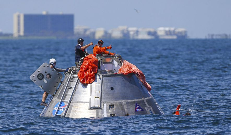 In this Thursday, July 13, 2017 photo, NASA astronaut Victor Glover signals back up to astronaut Daniel Burbank that he is OK after jumping into the Gulf of Mexico from the Orion capsule the astronauts are using to practice an emergency egress situation during recovery testing about four miles off of Galveston Island, Texas. The testing is the first time since the Apollo program that NASA has practiced such egress techniques from a capsule in open water. (Mark Mulligan/Houston Chronicle via AP)